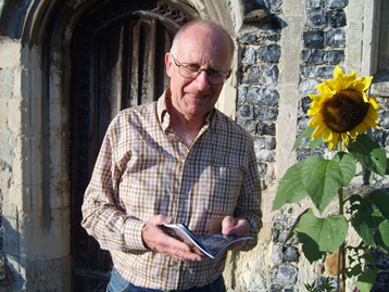 Clive outside one of the churches beside a sunflower.